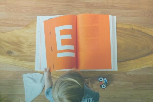 Criança Lendo Um Grande Livro Com Páginas Laranjas.