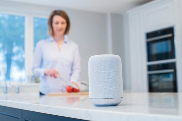 Mulher Utilizando Um Smart Speaker Na Cozinha.