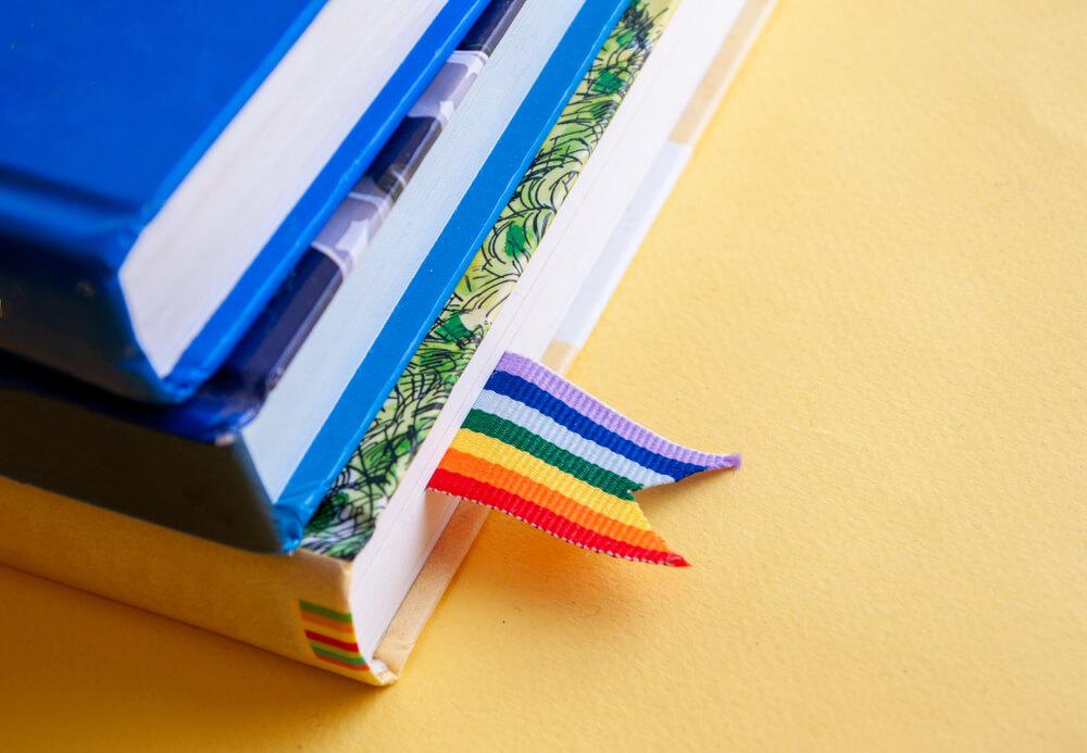 Três Livros Colocados Um Sob O Outro Com Um Marcador De Páginas Com As Cores Do Arco-íris No Primeiro Deles.