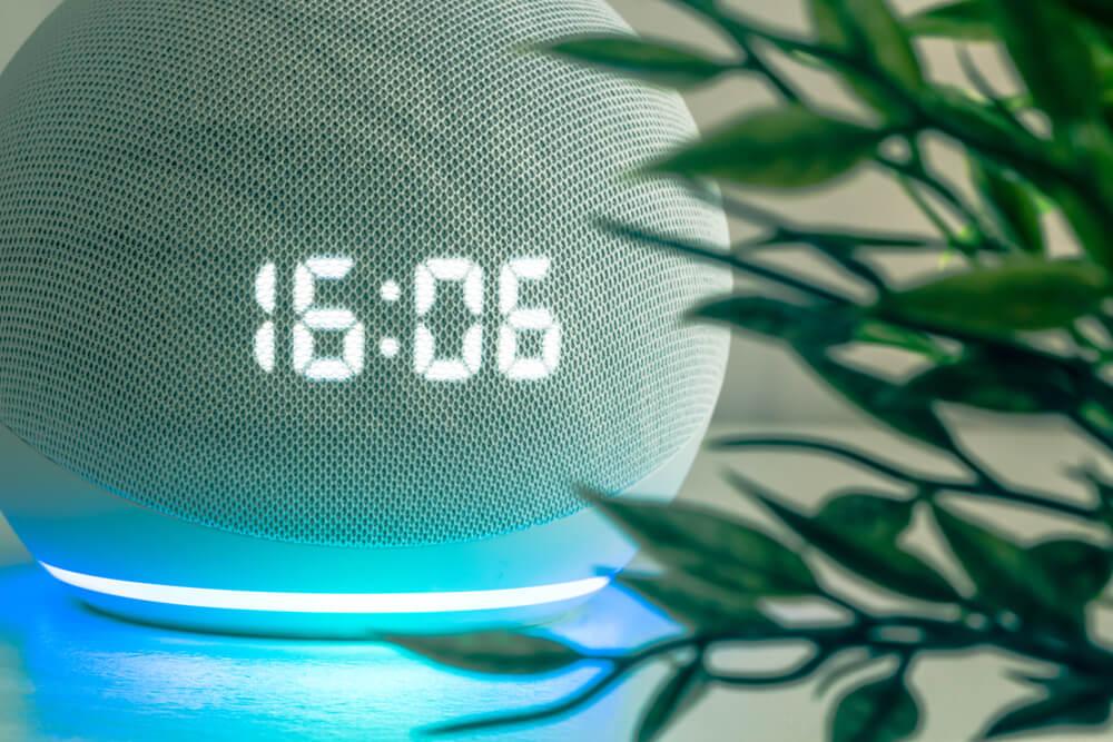 Alexa com relógio na cor branca em cima da mesa, com planta ao lado.