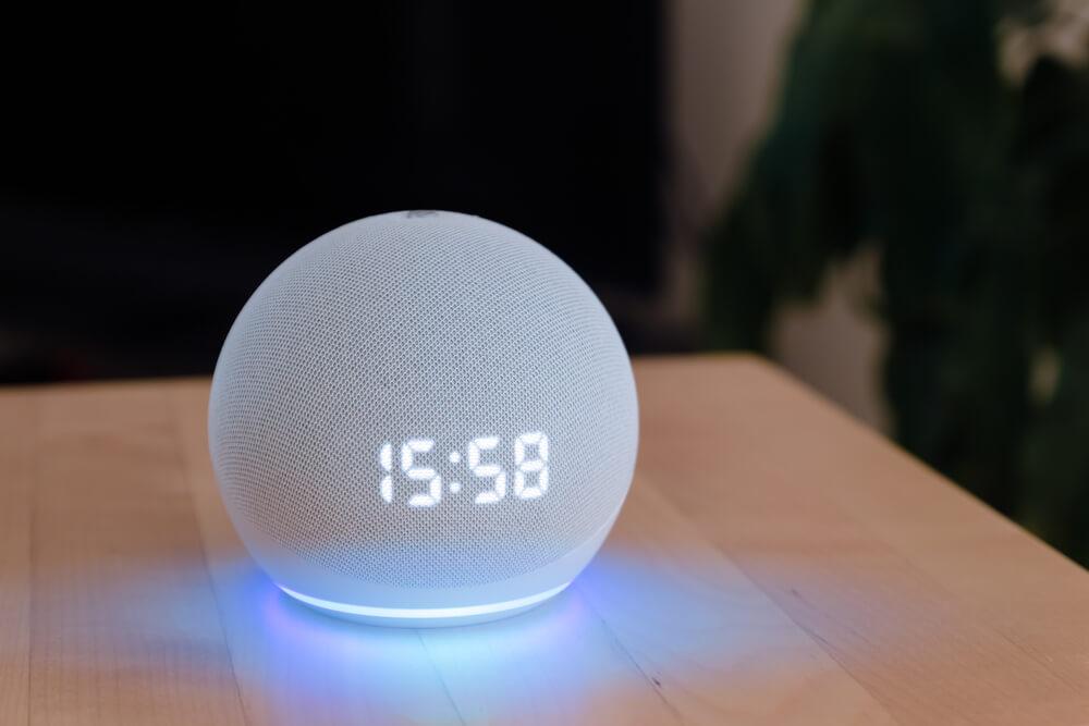 Alexa na cor branca, com relógio, em cima da mesa.