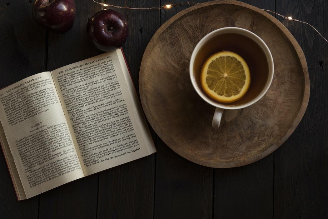Livro Aberto Com Xícara De Chá Ao Lado E Maçãs Acima.