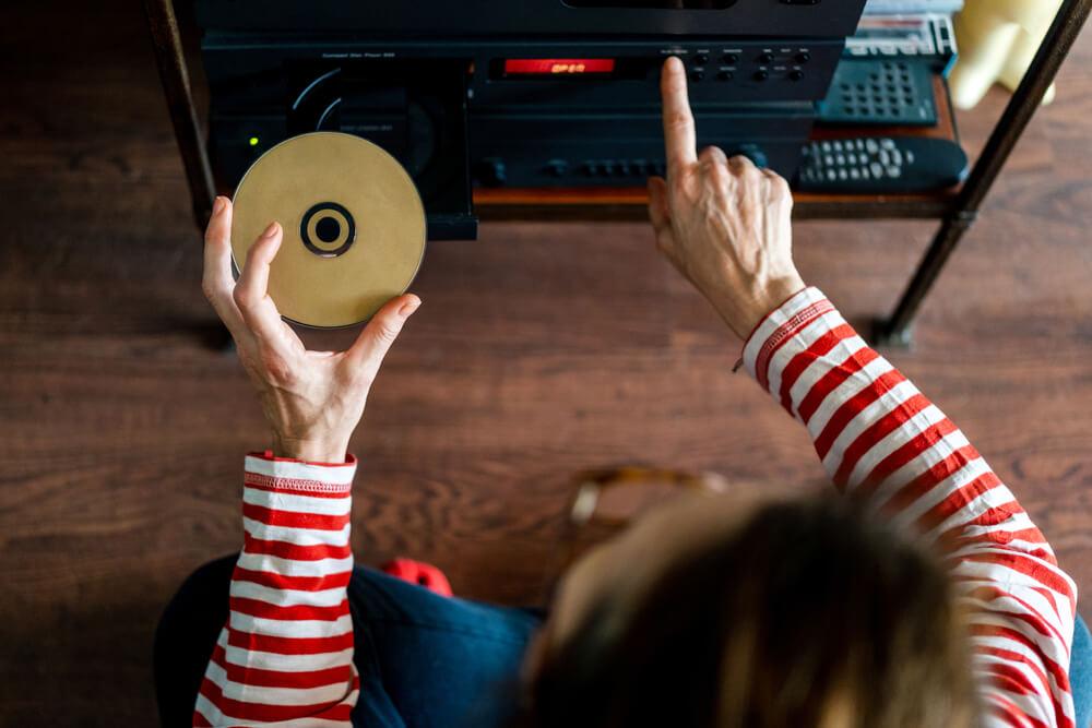 Mulher Ligando Rádio, Enquanto Segura Um CD Na Outra Mão.