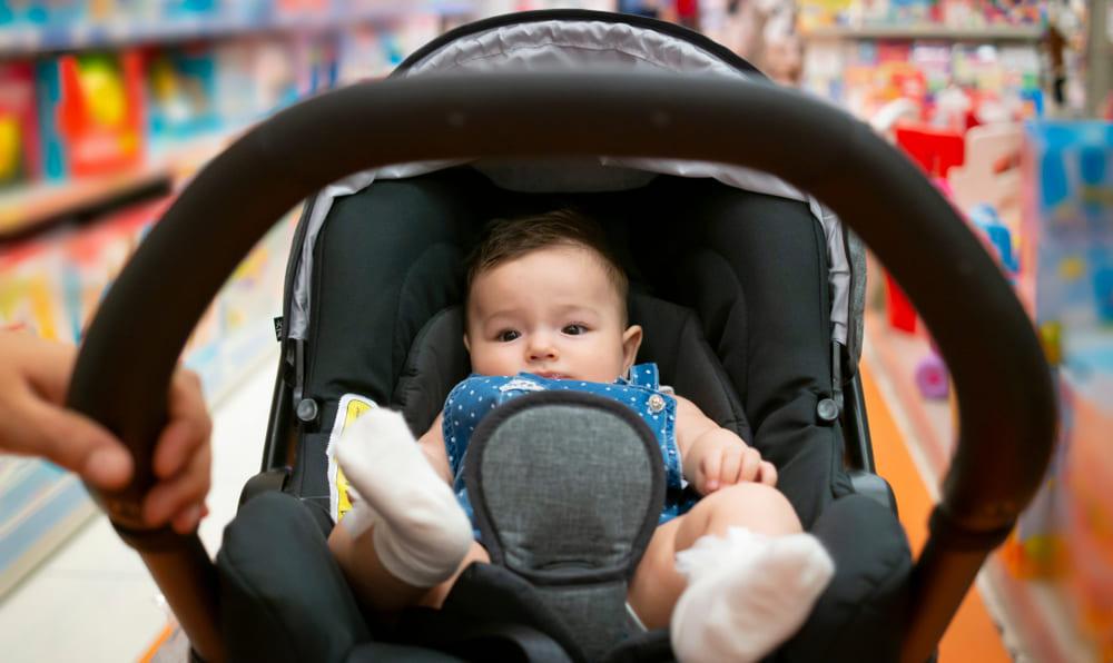 Neném Dentro Do Carrinho De Bebê Sendo Empurrado Por Uma Pessoa.