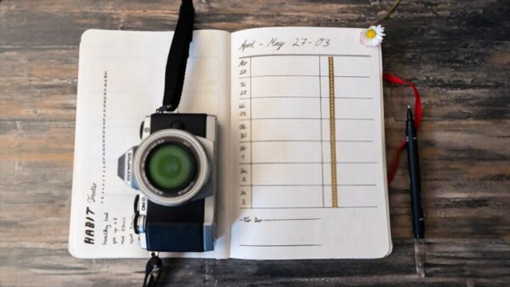 Caderno para bullet journal barato com câmera digital em cima.