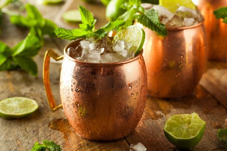 Drink Gin Gin Mule em uma caneca dourada, com gelo e hortelã.