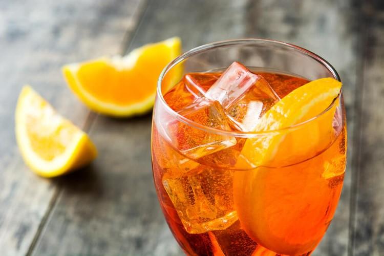 Drink London Spritz com gin, aperol, gelo e rodelas de limão.