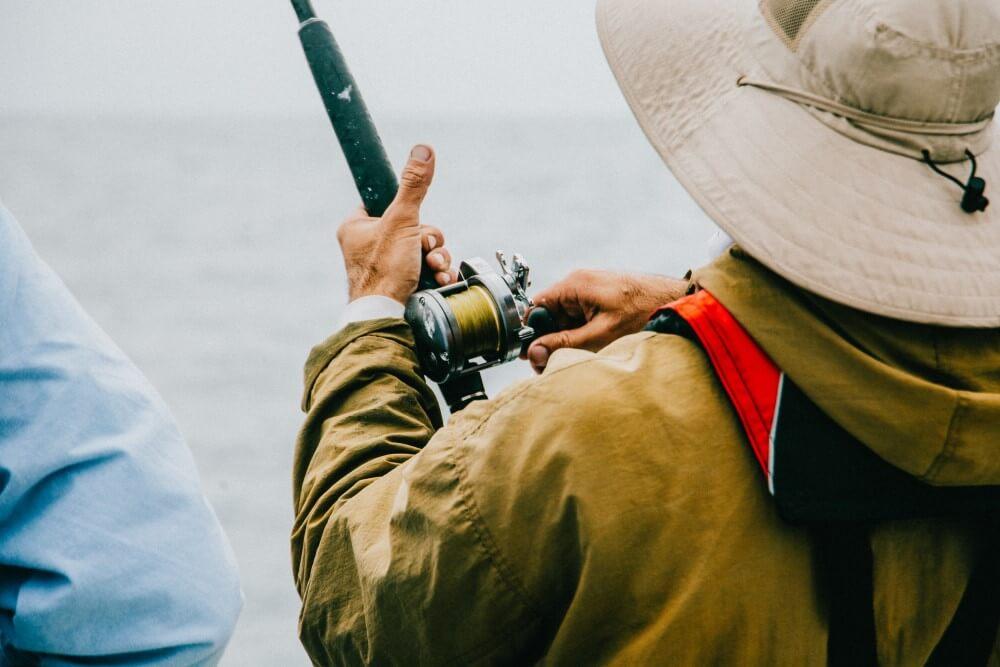 Homem Pescando Em Um Barco Com A Melhor Carretilha De Pesca Em Mãos