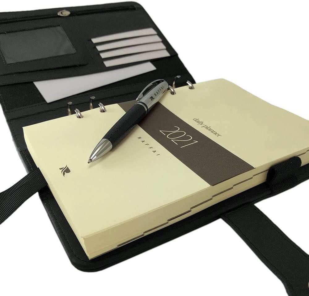 Planner 2021 aberto, com caneta por cima, capa na cor preta.