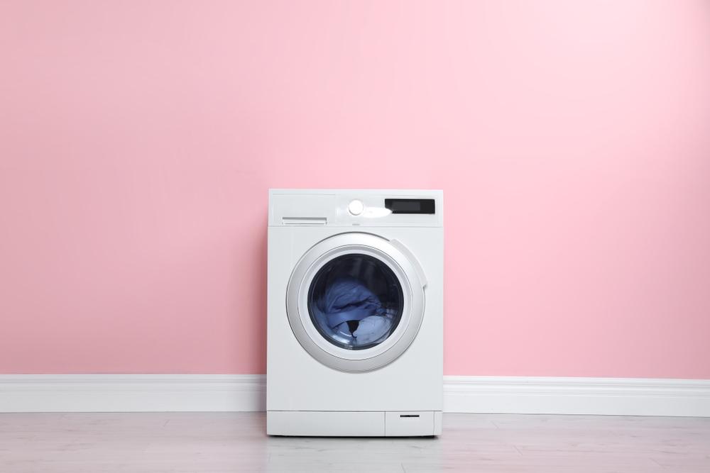 Máquina De Lavar Roupas Em Frente De Parede Rosa.