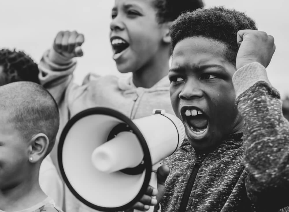 Criança negra gritando em um megafone durante protesto.