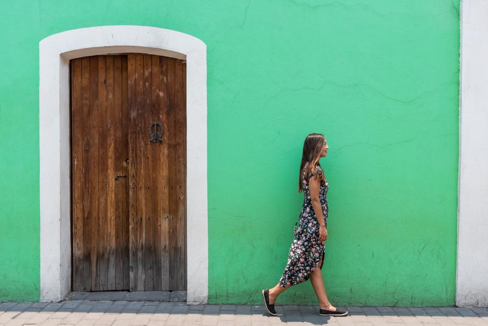 Mulher Caminhando Em Frente De Uma Casa Verde, Enquanto Veste Um Vestido Longo De Verão.