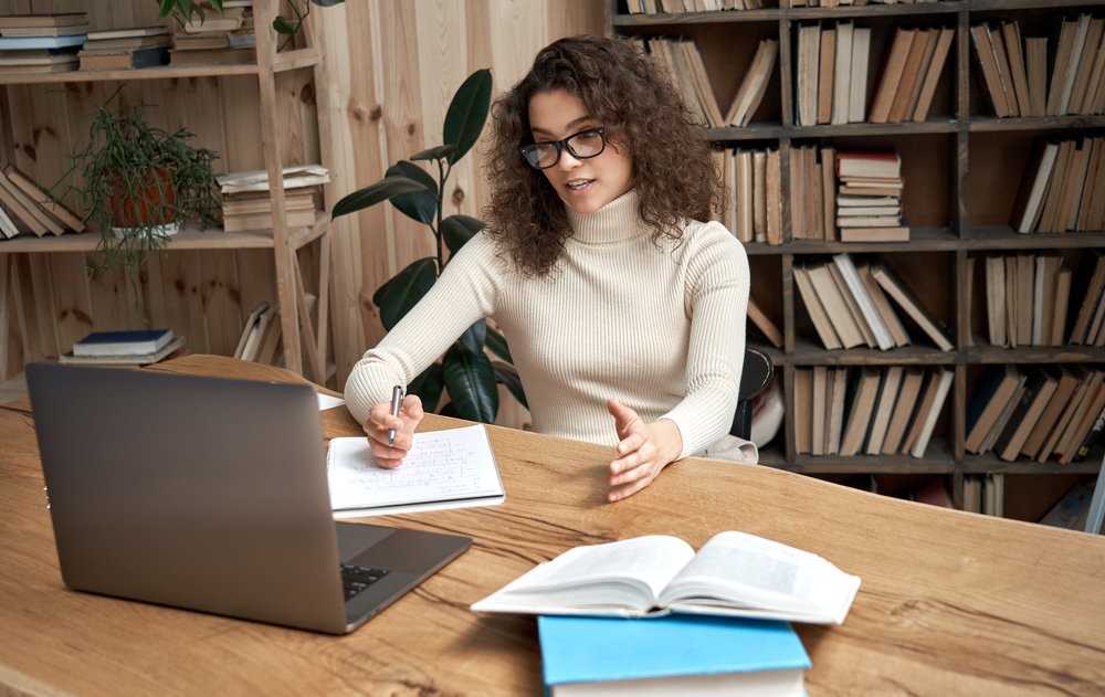 Mulher Sentada Em Uma Mesa, Enquanto Escreve E Olha A Tela Do Computador. Ao Fundo, Há Uma Estante De Livros.