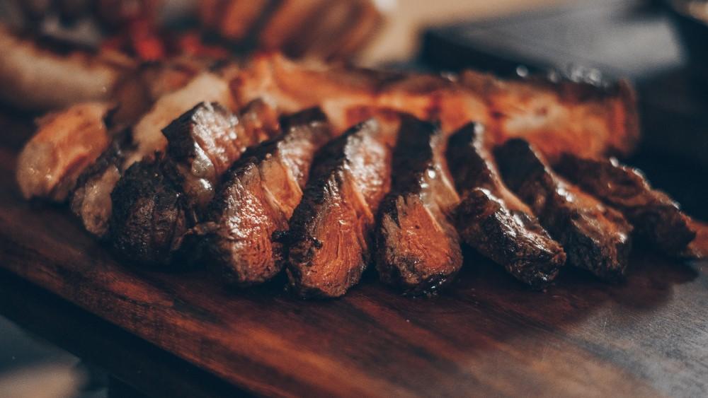 Tábua De Madeira Para Churrasco. Em Cima, Uma Carne De Churrasco Cortada