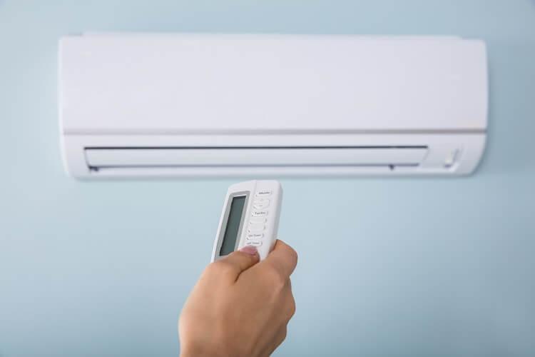Mão apontando controle para ar-condicionado.