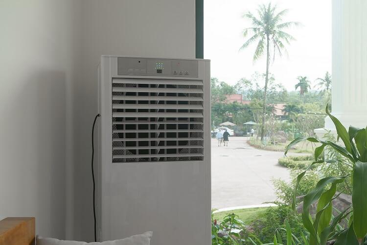 Ar-condicionado portátil colocado perto de uma janela com vista para várias folhagens.