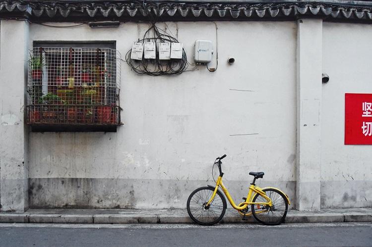 Bicicleta amarela encostada em um meio fio.