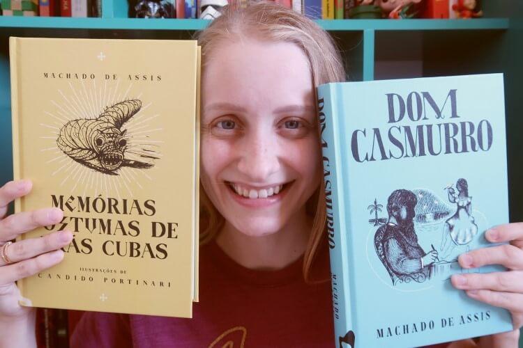 Pessoa segurando os dois livros: Memórias póstumas... e Dom Casmurro.