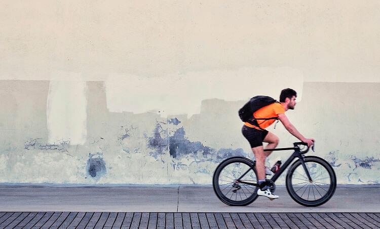 Homem de mochila andando de bicicleta.