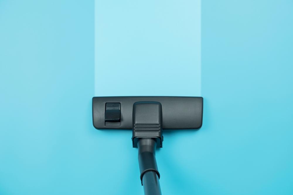 Aspirador De Pó Vertical Limpando Tapete Da Cor Azul.