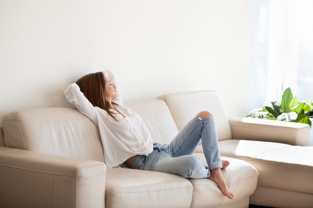 Mulher Deitada Em Um Sofá Moderno E Confortável, Relaxando.