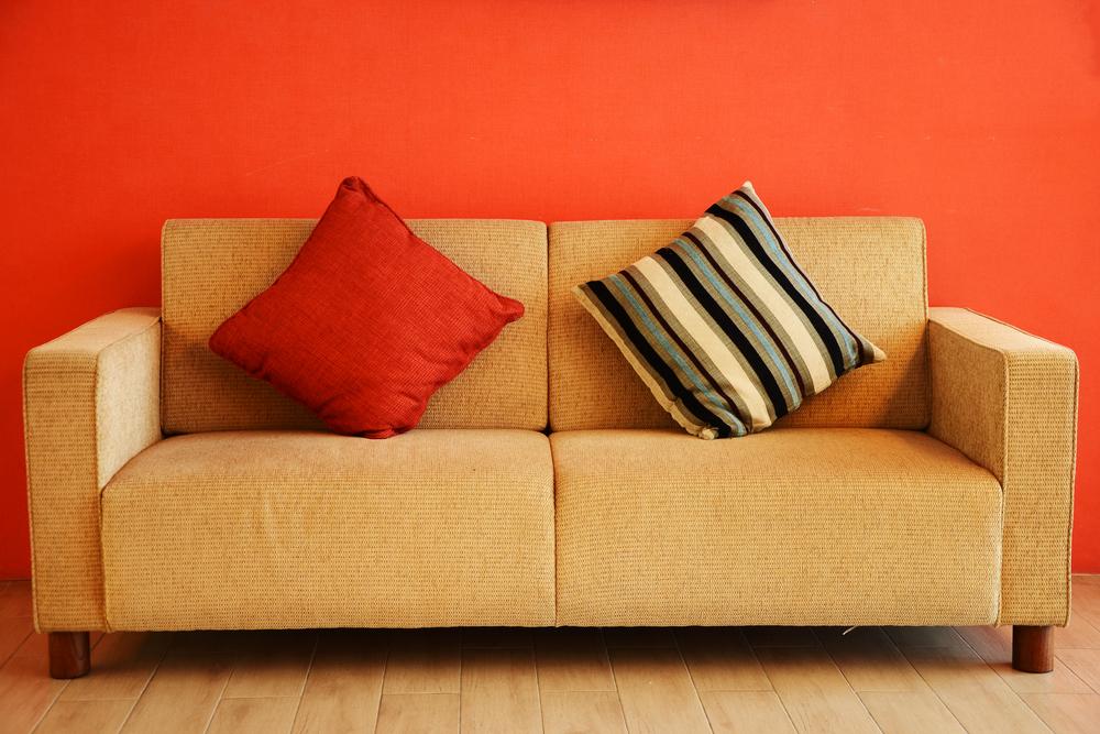 Sofá de cor neutra, com duas almofadas, colocado na frente de uma parede na cor laranja.