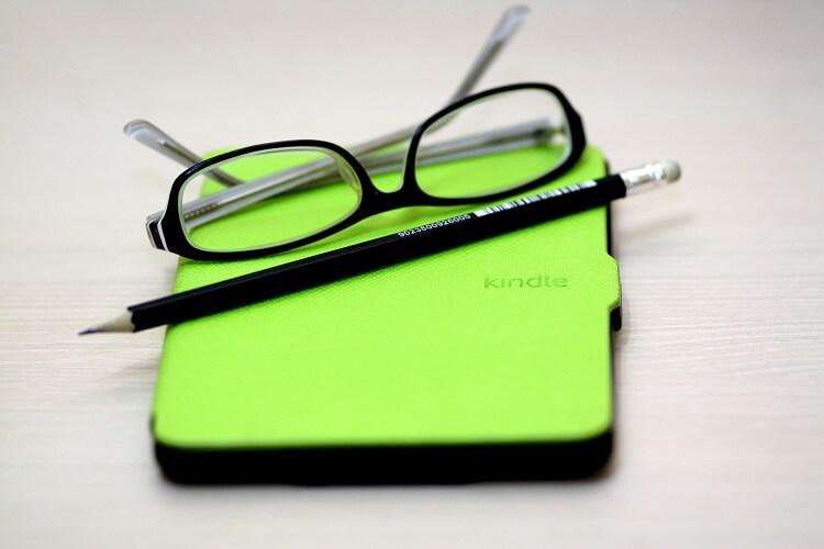 Kindle de capa verde com óculos preto em cima