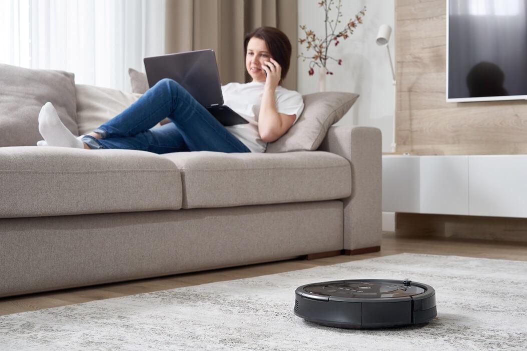 Melhor Robô Aspirador: Mulher Sentada No Sofá Enquanto Aspirador Robô Limpa A Casa