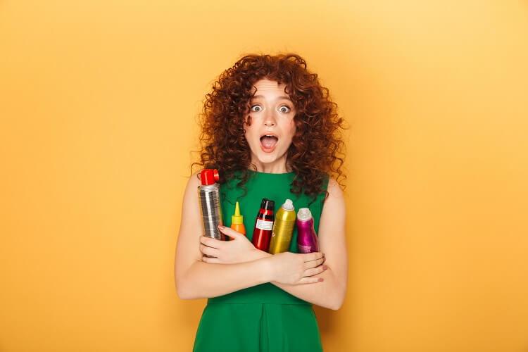 Mulher ruiva segurando produtos de cabelo.