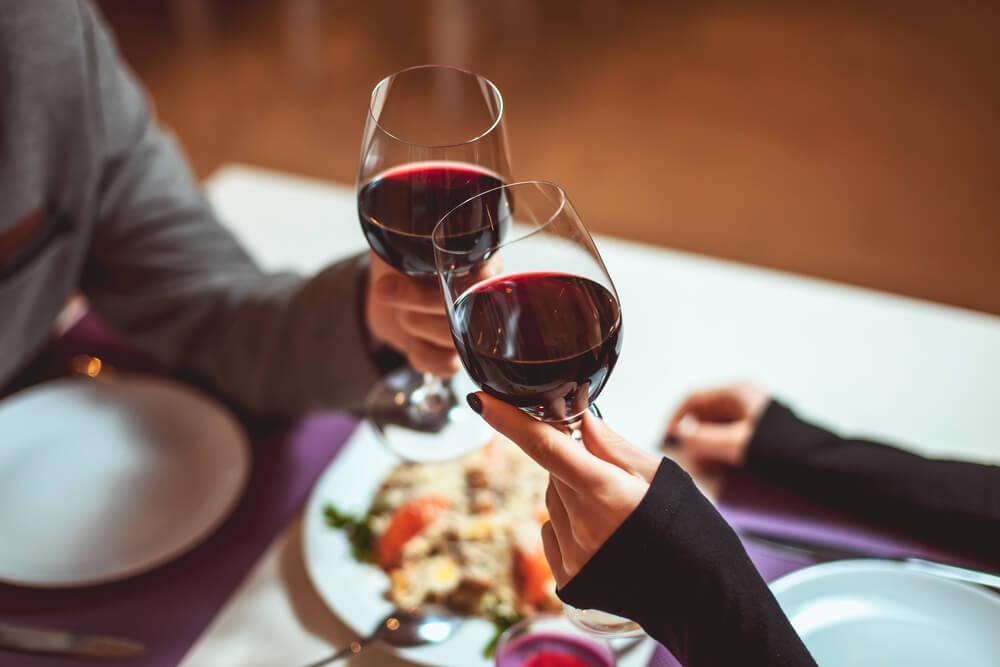 Casal Fazendo Um Jantar Com Vinho Tinto E Brindando Com As Taças.