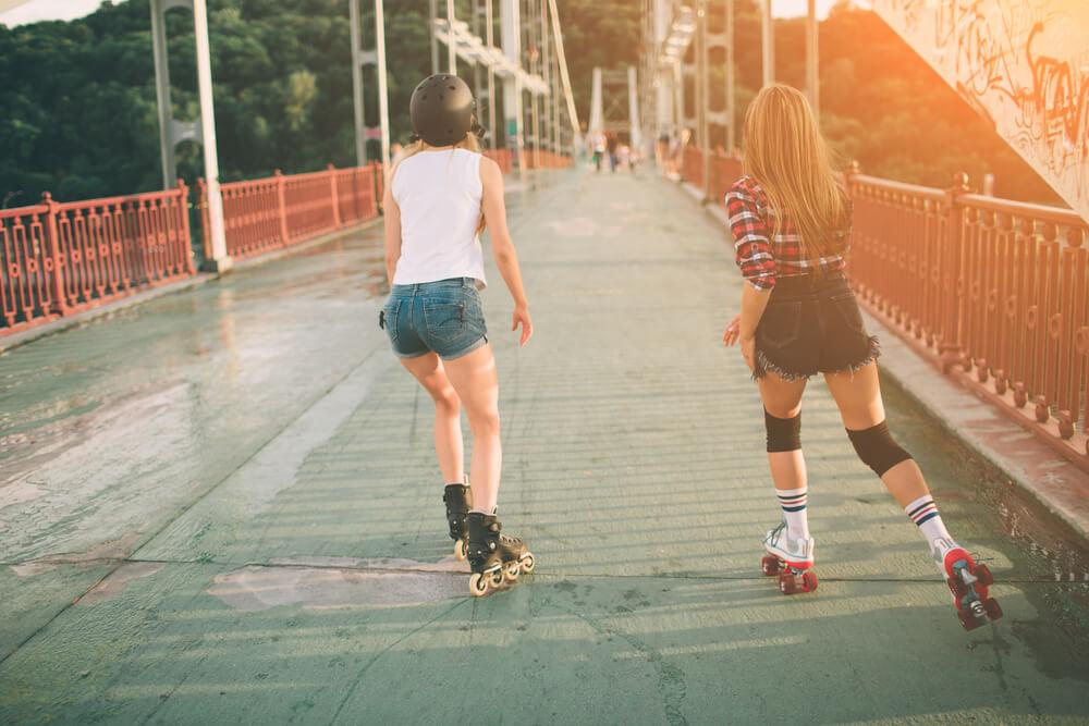 Garotas patinando. Uma está com o quad e a outra com o inline.