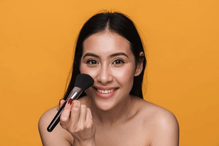 mulher aplicando bb cream para pele oleosa com pincel
