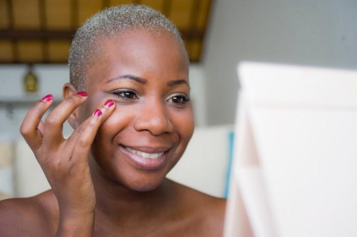 mulher aplicando bb cream para pele oleosa com os dedos