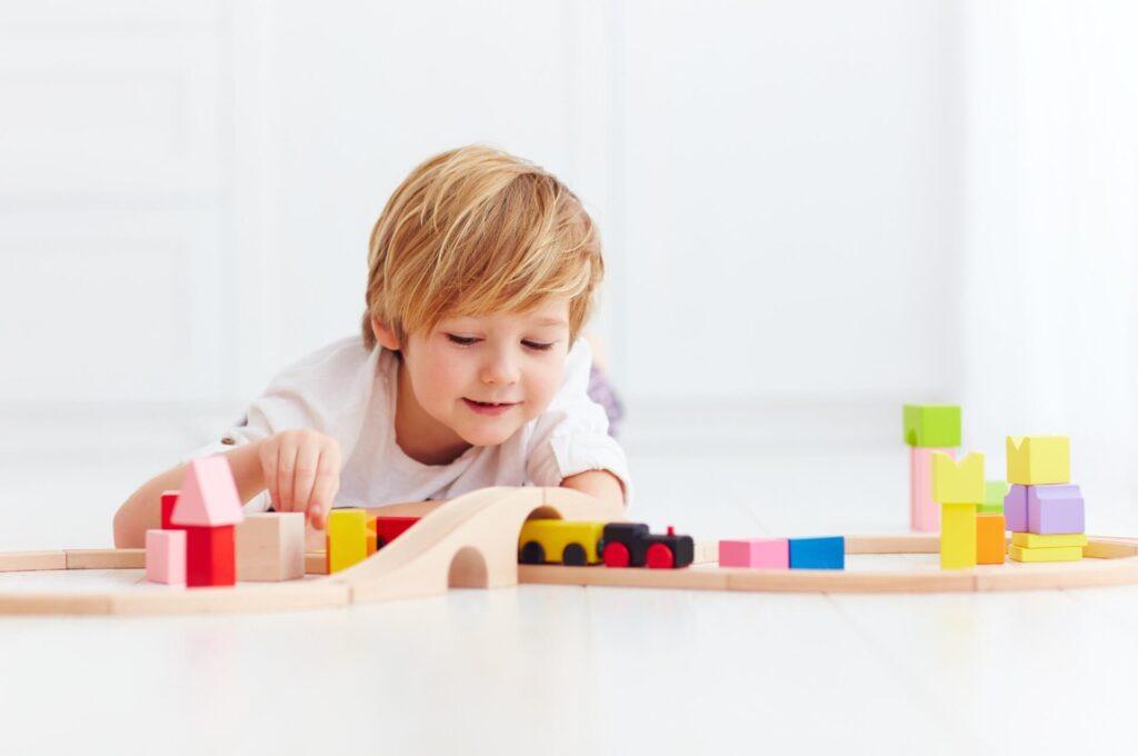 Menininho brinca com brinquedos de madeira