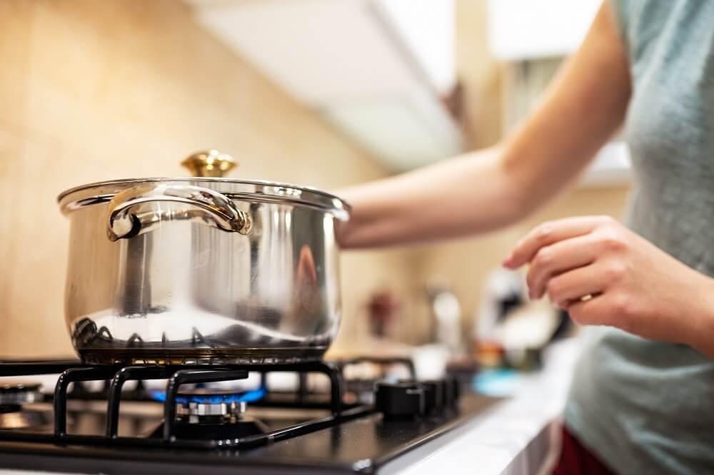 Mãos femininas mexendo em panela sob fogão