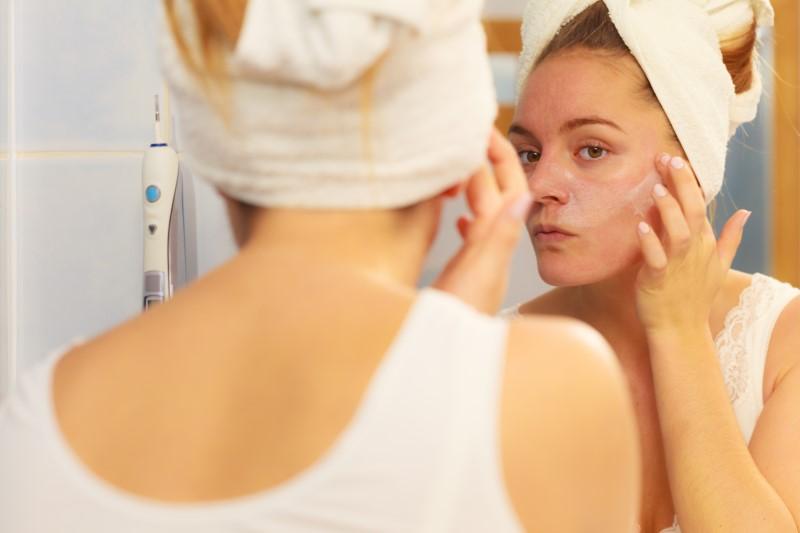 mulher olhando sua pele no espelho