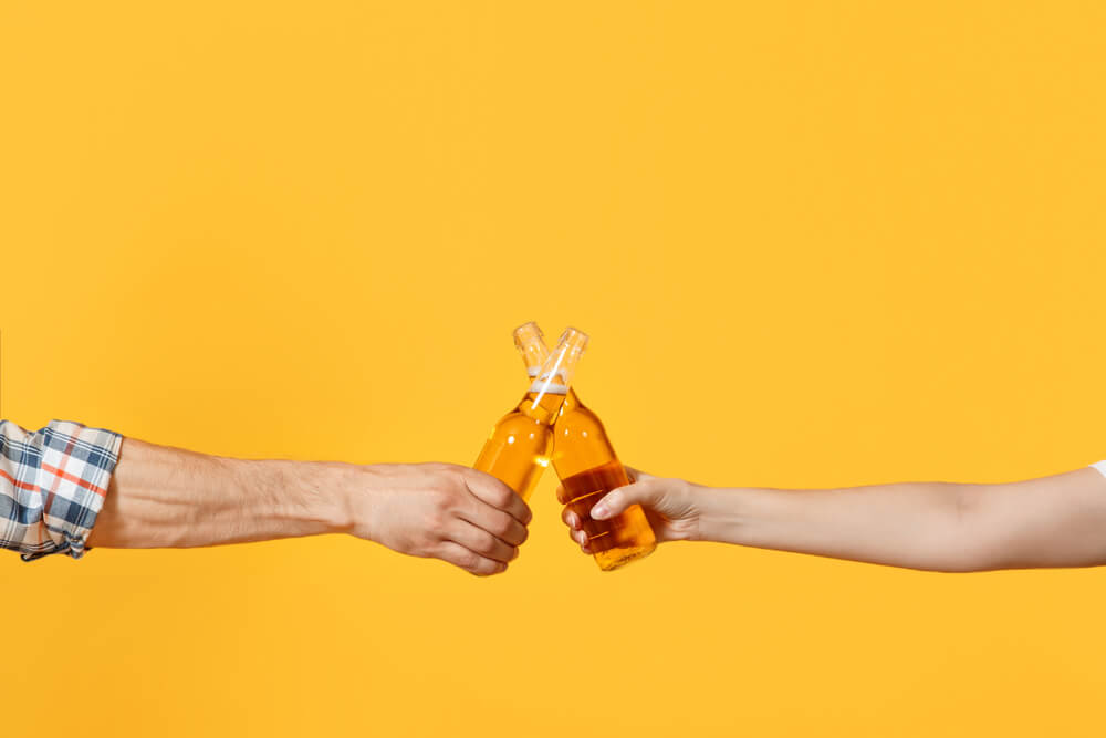 Dois Braços Segurando Cada Um Uma Garrafa De Cerveja, Em Um Fundo Amarelo.