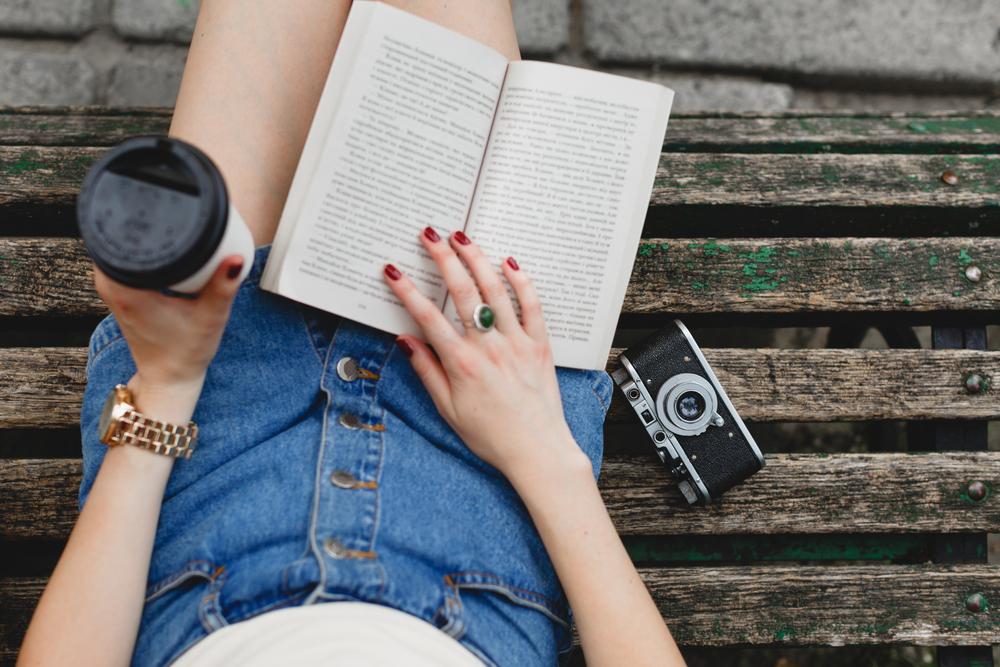 Menina Sentada Em Um Banco, Usando Uma Saia Jeans, Lendo Um Livro, Com Uma Câmera Ao Lado E Um Copo De Café Em Uma Das Mãos.