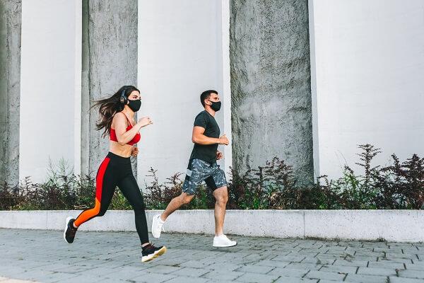 dupla de corredores correndo ao ar livre com máscara de proteção