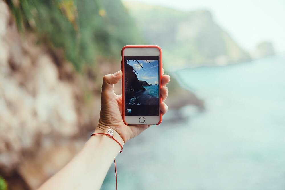 Mão segurando celular para fotografar paisagem de praia