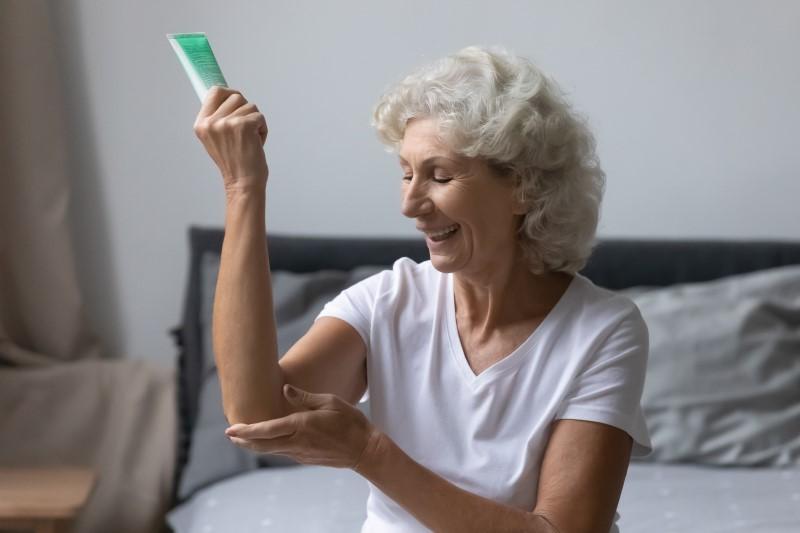 Senhora aplicando hidratante no cotovelo