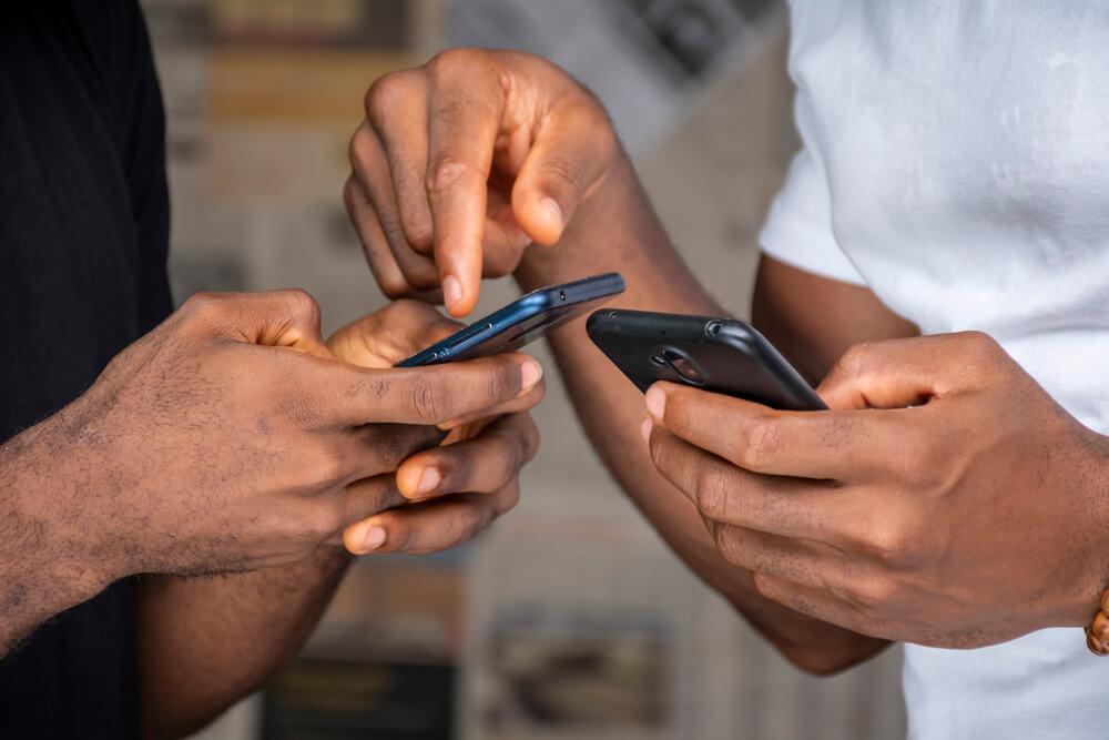 Close Na Mão De Dois Homens Negros, Cada Um Está Segurando Um Aparelho Celular Diferente.