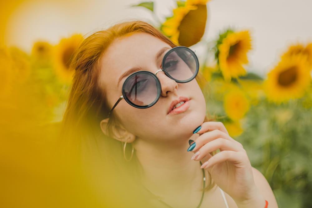 Mulher Entre Uma Plantação De Girassois Utilizando Um óculos Diferente De Sol.