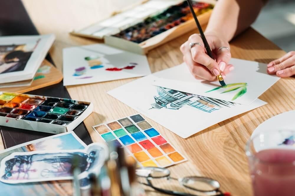 Mãos femininas desenhando em aquarela