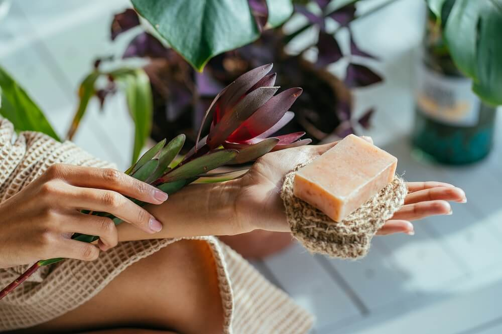 Mãos Femininas Segurando Flores E Sabão Em Barra Com Discos De Crochê Para Limpar O Rosto.