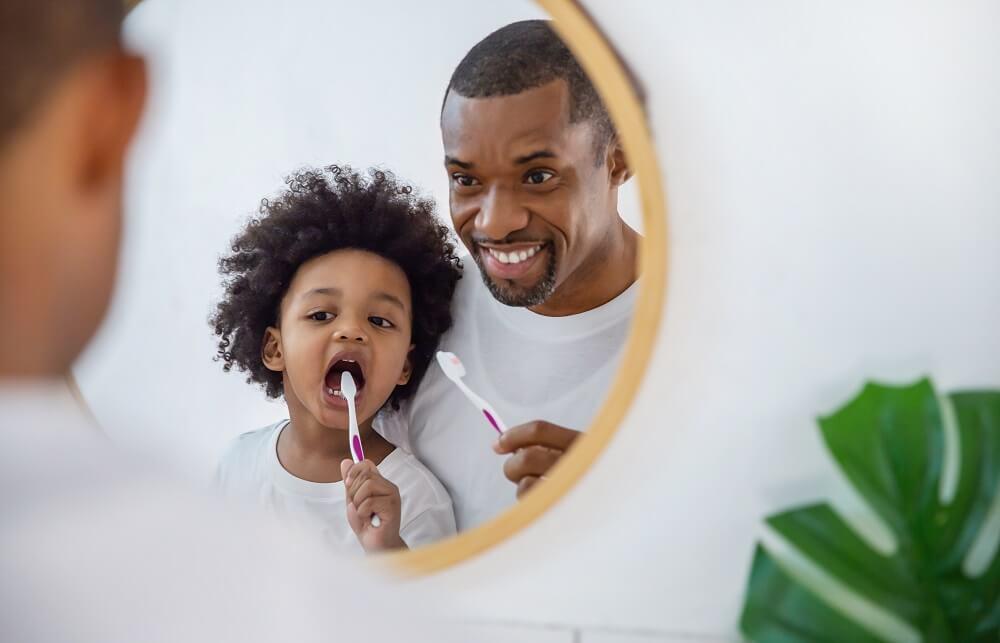 Pai e filho negros, escovando os dentes enquanto se olham em um espelho redondo
