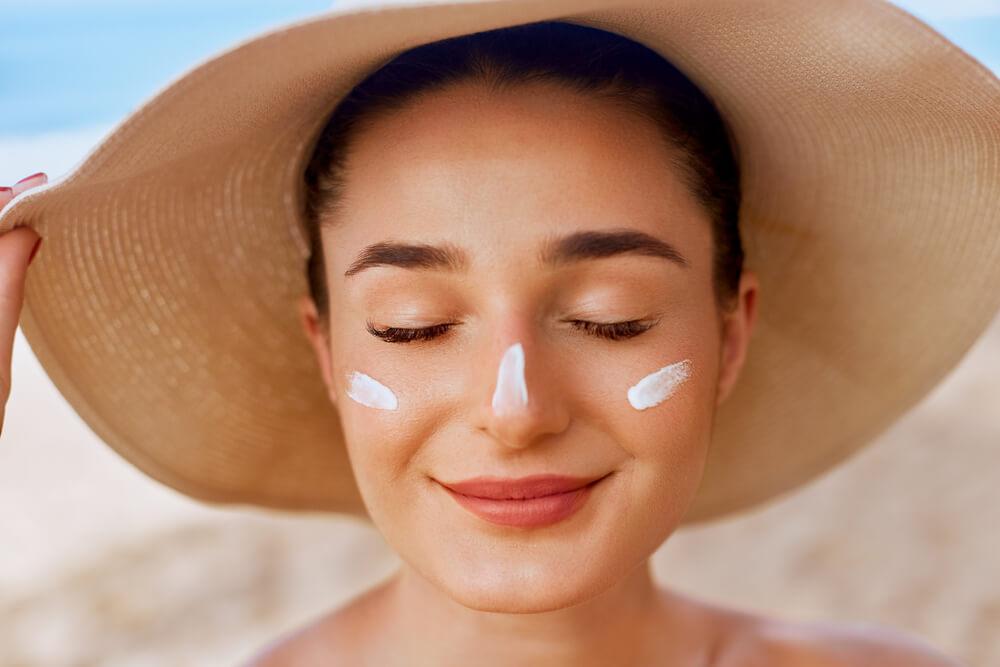 Mulher Branca Em Uma Praia, Usando Um Chapéu E Com Protetor Solar Facial No Rosto, Com Riscos Do Creme Nas Bochechadas E No Nariz.