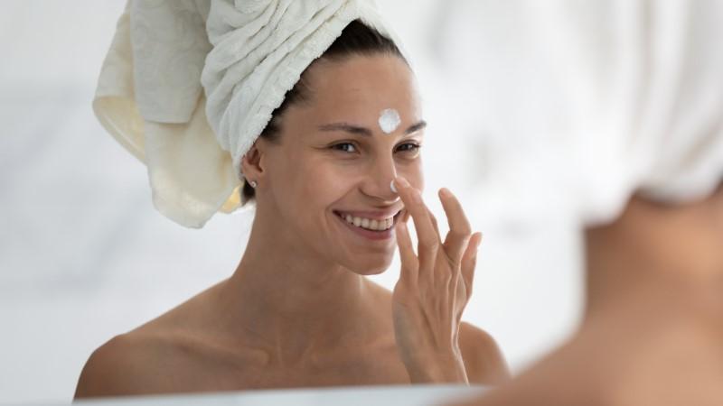 mulher aplicando protetor no rosto