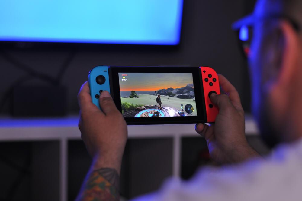 Pessoa Jogando Nintendo Switch Nas Cores Azul E Vermelha.