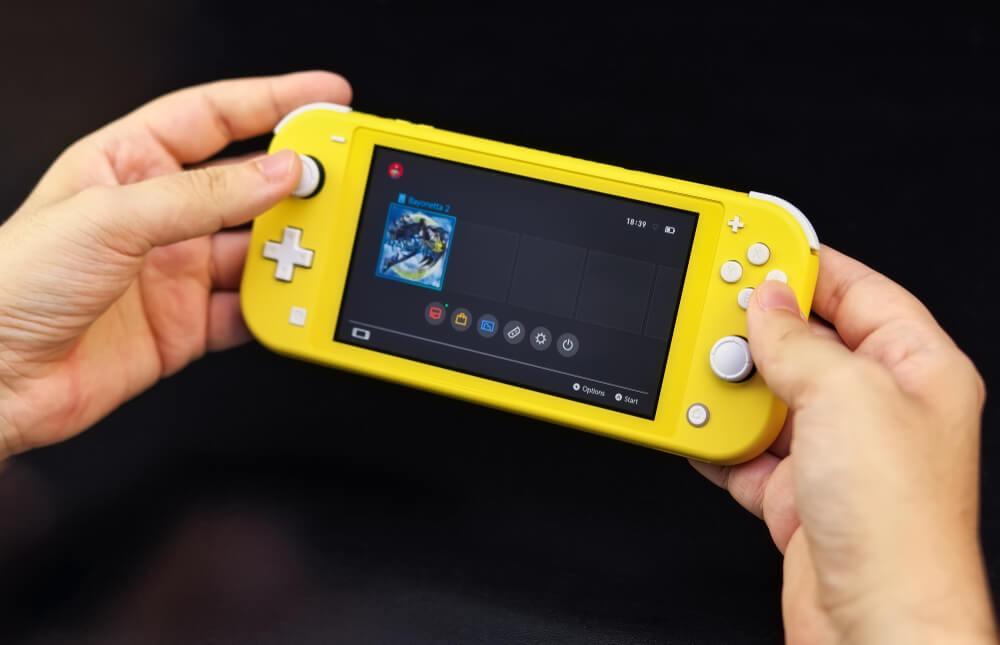 Nintendo Siwtch Lite amarelo nas mãos de uma pessoa.